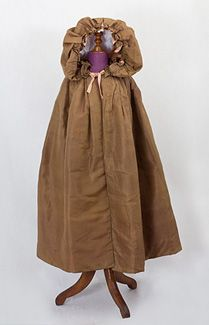 Girl's silk cloak, c.1790-1820. The hand sewn cloak is fashioned from brown silk and is lined with pink glazed cotton. It is padded for warmth and closes in front with two sets of ties. The neckline has a double row of ruffles that show when the hood is down. The fullness of the hood can be adjusted by a silk ribbon drawstring tie. Amazingly for a 200-year-old cloak, the condition is almost excellent and all original.