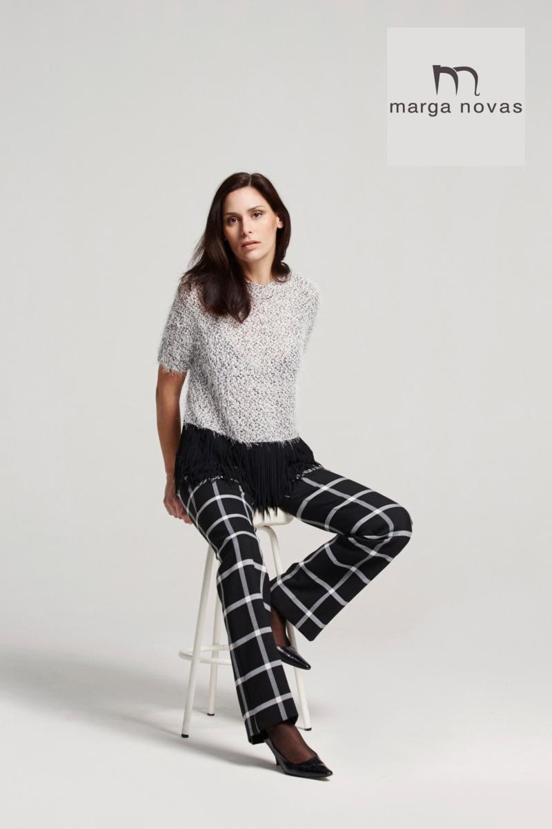 La combinación blanco y negro es siempre un acierto y en esta temporada te proponemos un original pantalón de fondo negro y cuadro blanco que podrás combinar con un top que mezcla estos colores con un actual acabado en flecos negros.