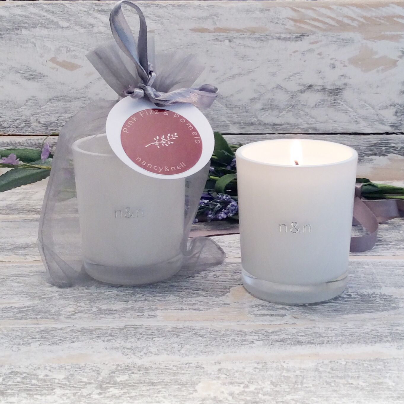 A pink fizz pomelo votive candle presented in a
