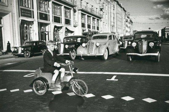 «Мальчик на велосипеде, работающем на бензине, пересекает ул. Горького». Автор Аркадий Шайхет, 1935 год.