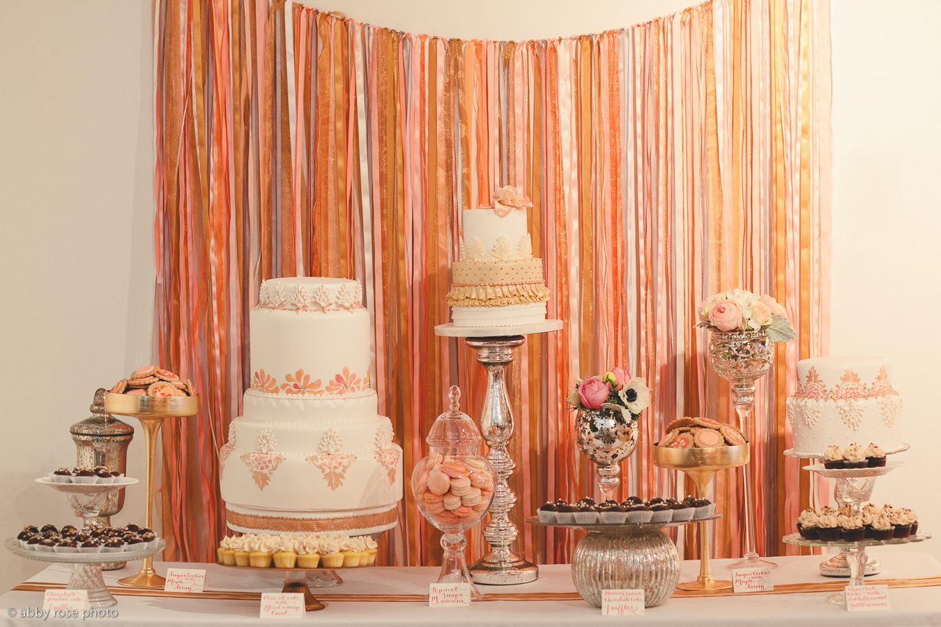 Example of vintage glam inspired dessert table - use of mercury glass mixed with other vintage pieces, not symmetrical, differing heights of stands and florals