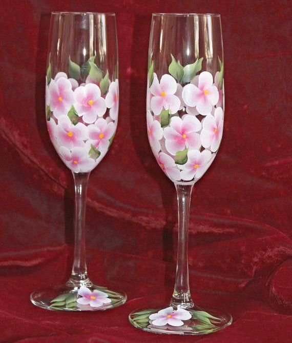 Conjunto de dos elegantes mano pintado flautas de champán con hortensias rosas y blancas en un cristal. Perfecto para una fiesta nupcial o una boda. También puede ser dado como un regalo de aniversario, regalo de cumpleaños, o simplemente porque...  Si las gafas son un regalo que yo sería feliz con una tarjeta de regalo con tu mensaje personal. Además cada vaso se puede personalizar mediante la adición de nombres y fecha a la base, generalmente en color oro. Para cualquier solicitud solo…