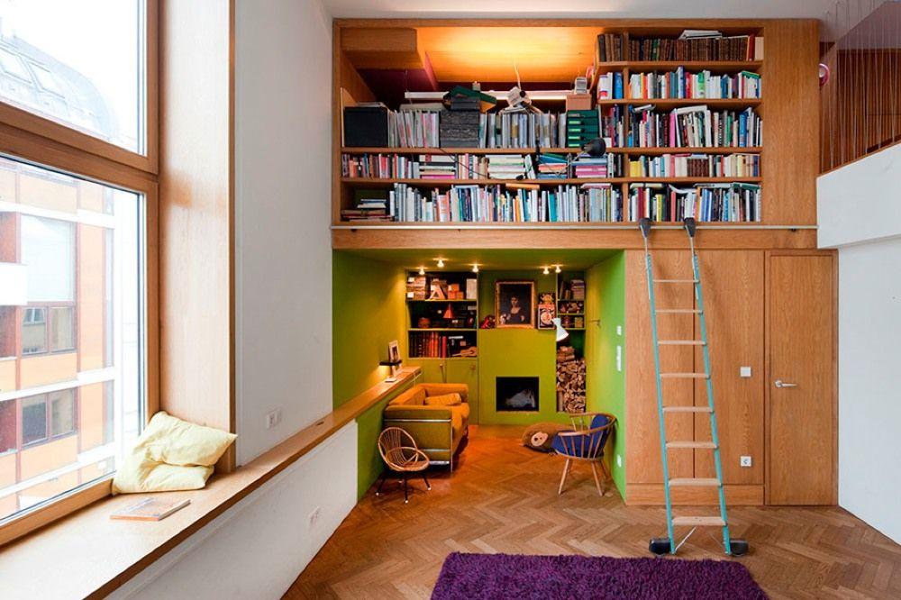 コンパクトなソファスペースの上にある作り付けの巨大本棚 | 住宅デザイン