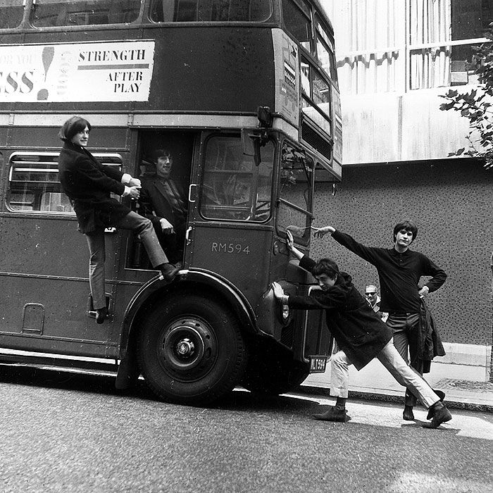 The Kinks joke around with a double-decker bus on a London street on Sept. 7, 1964.