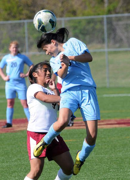 Cape's Stephanie Mendez heads the ball away from a Bucs midfielder. Click soccer photo to read entire sports article: Cape girls soccer ties Bucs 2-2