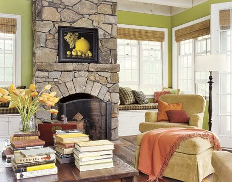 a rustic stone fireplace adds contrast to this otherwise modern and colorful living room