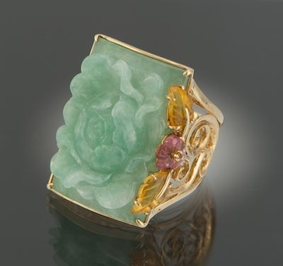 A Carved Jadeite Ring and Citrine Ring. 14k yellow gold ring with open scroll design shoulders, featuring a carved jadeite plaque depicting a chrysanthemum flower, with carved citrine leaves and carved amethyst flower.