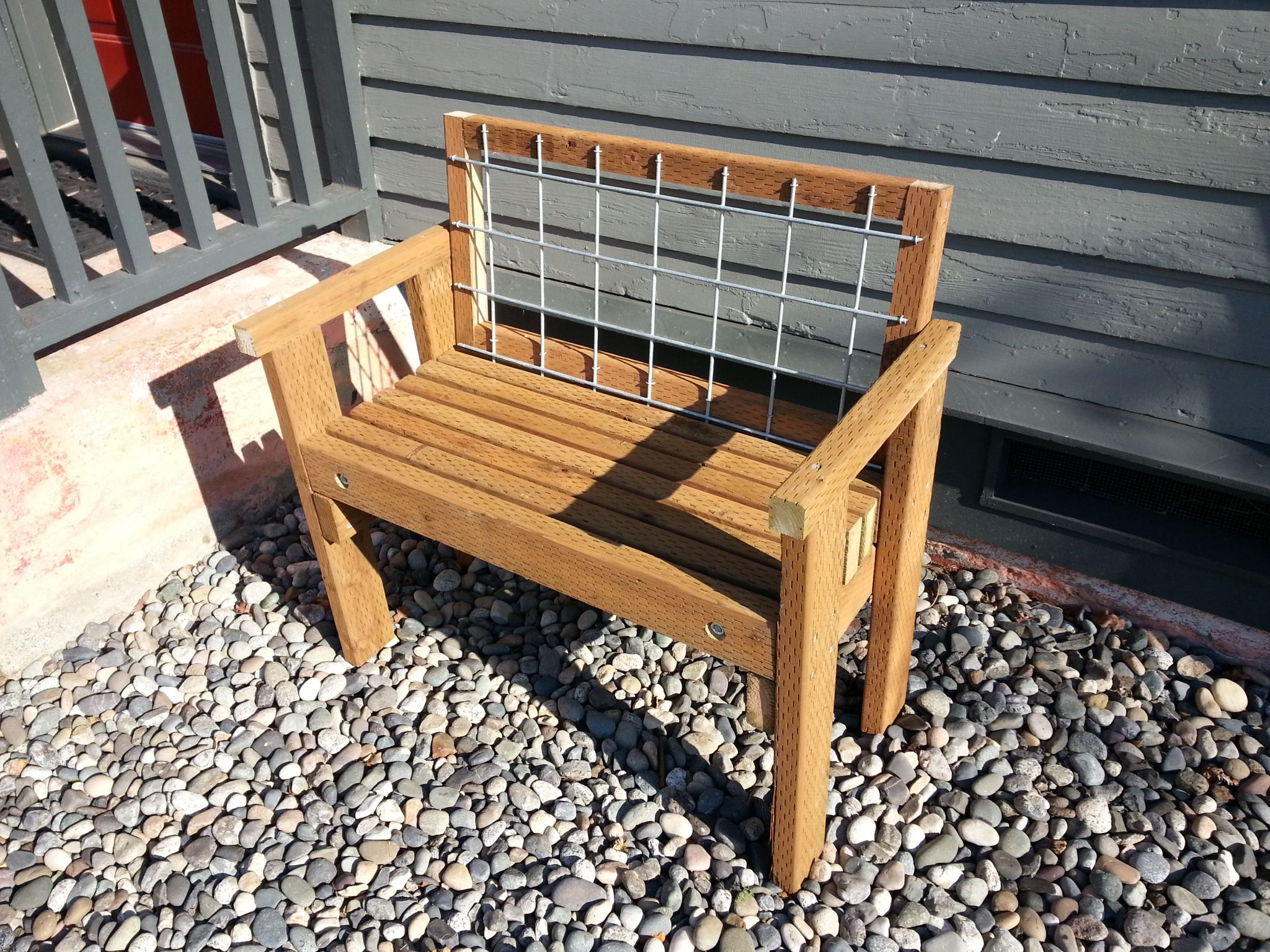 Rugged outdoor wood bench with hog wire back. Wood bench