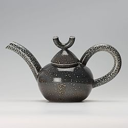 This is a thrown and assembled salt glaze macaroni teapot with a press moulded spout by Walter Keeler.