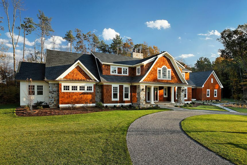 Traditional shingled mansion with palladian window, columned gambrel roofed entry and attached barn style garage and circular pebblestone paved driveway.