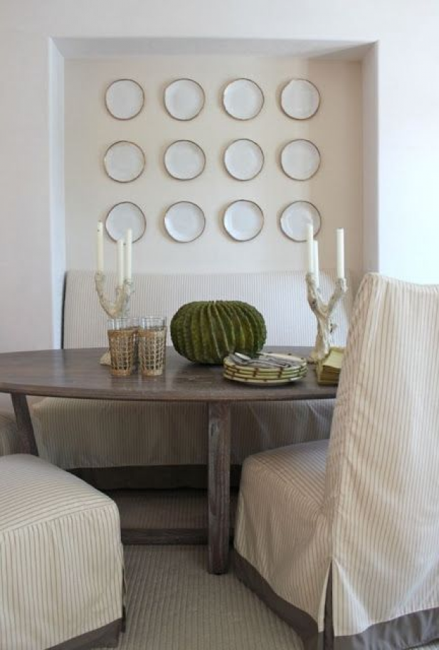Understated breakfast nook with handmade slightly irregular plates on display #diningroomdecor #coastal #dining #room #decor