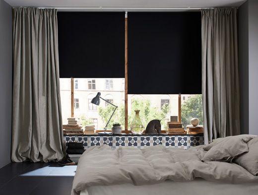 Ein Schlafzimmer, u. a. mit schwarzen Verdunklungsrollos vor den ...