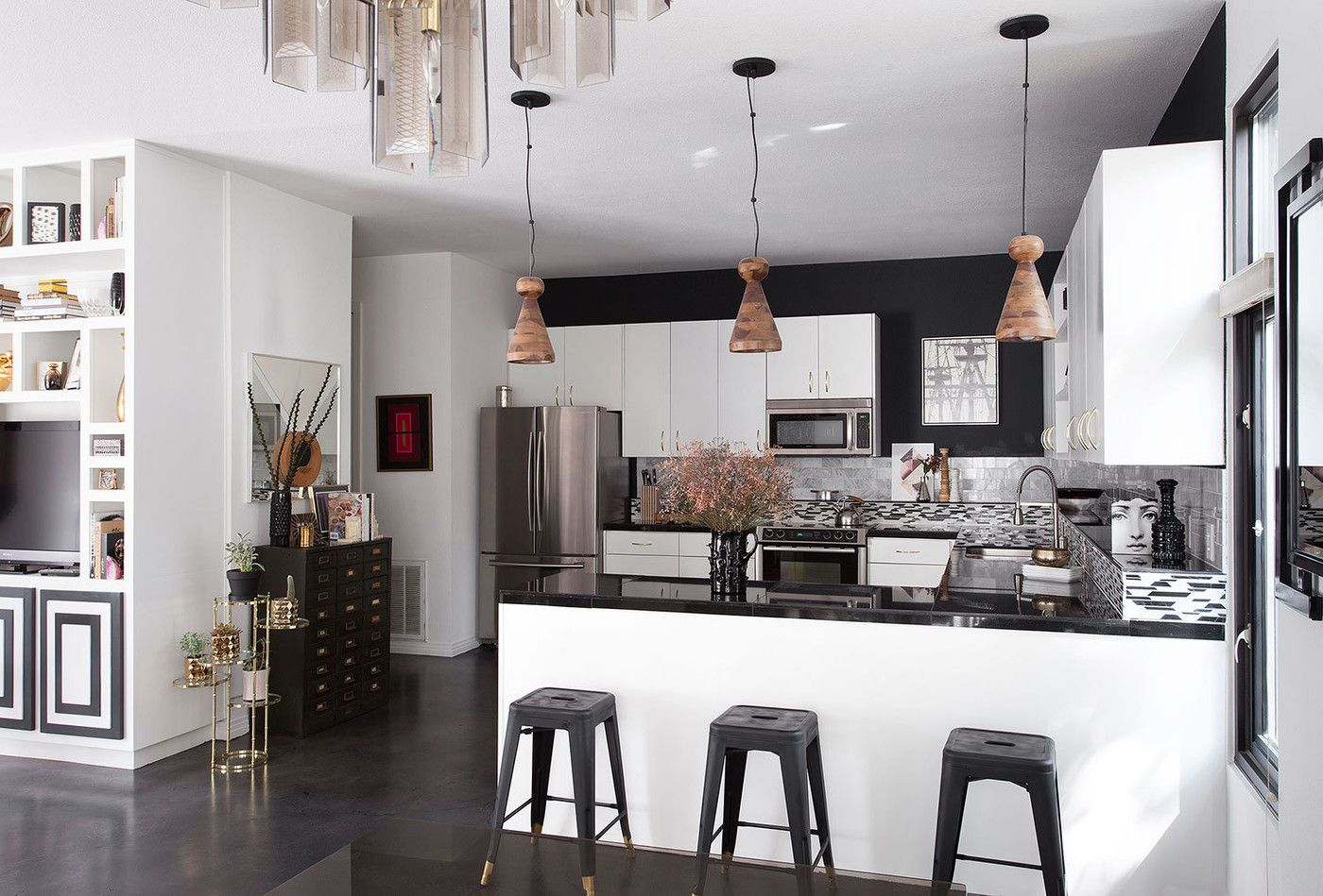 Contemporary Hollywood Regency Kitchen: A trio of pendant lamps hang over a black & white kitchen  .
