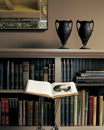 Organizing Collections:   Redoing this room allowed Martha to organize her garden books in a way that made sense; now each one is easy to find when she needs it. One of two large Art Deco mirrors hangs above the bookcase, visually extending the space.