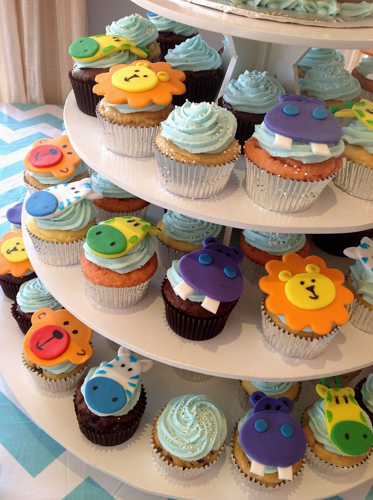 This rainbow-studded baby boy shower featured a small sculpted cake and matching cupcake tower. The cake was covered in textu...