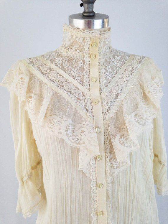 7e7a6e379a Victorian Inspired Blouse from the 1970s Features a high collar neckline  with floral lace and ribbon trim. Sheer gauzy cotton body completes the
