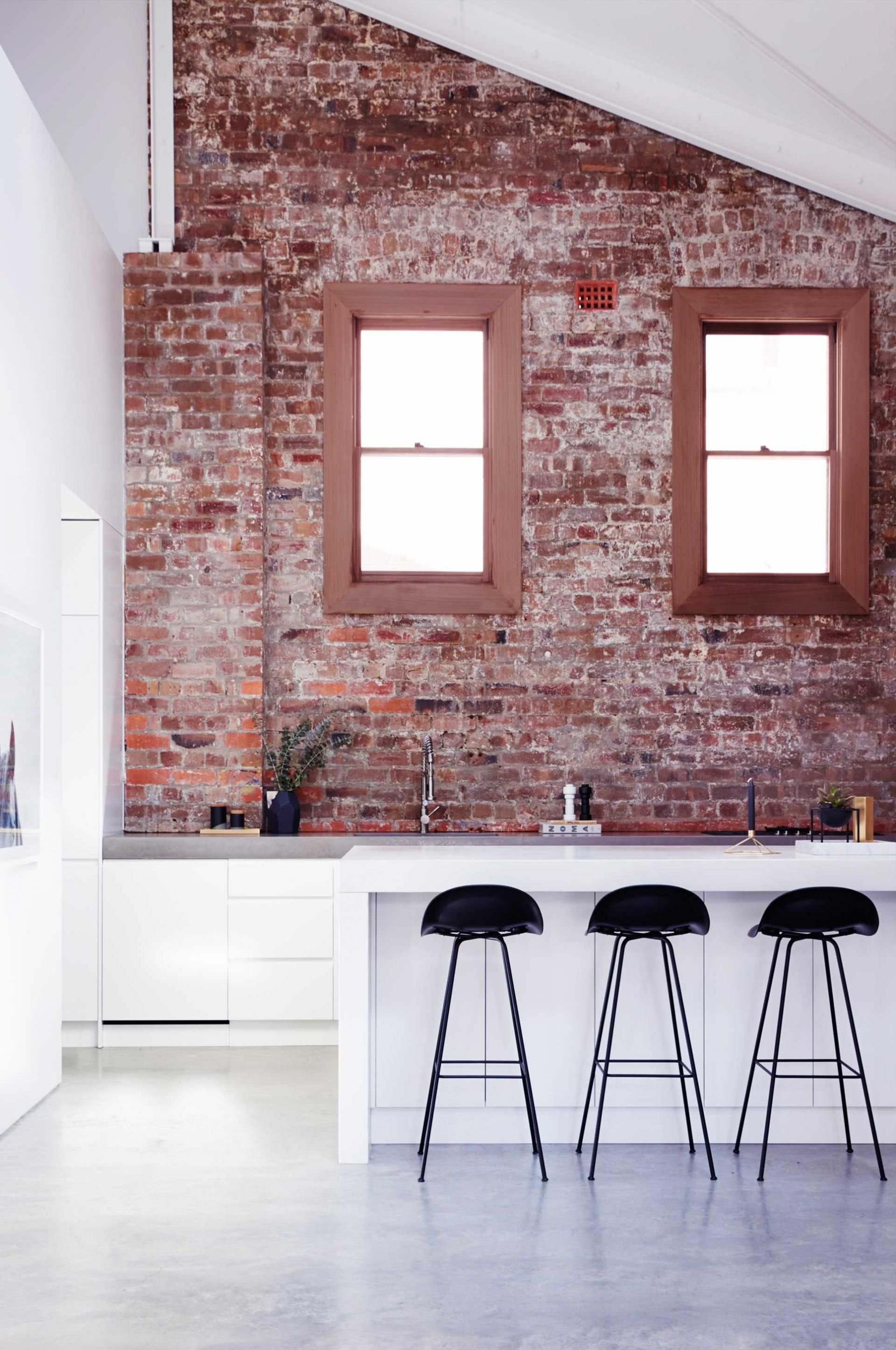 An Industrial Warehouse - Brick Walls And Black Counter Stools