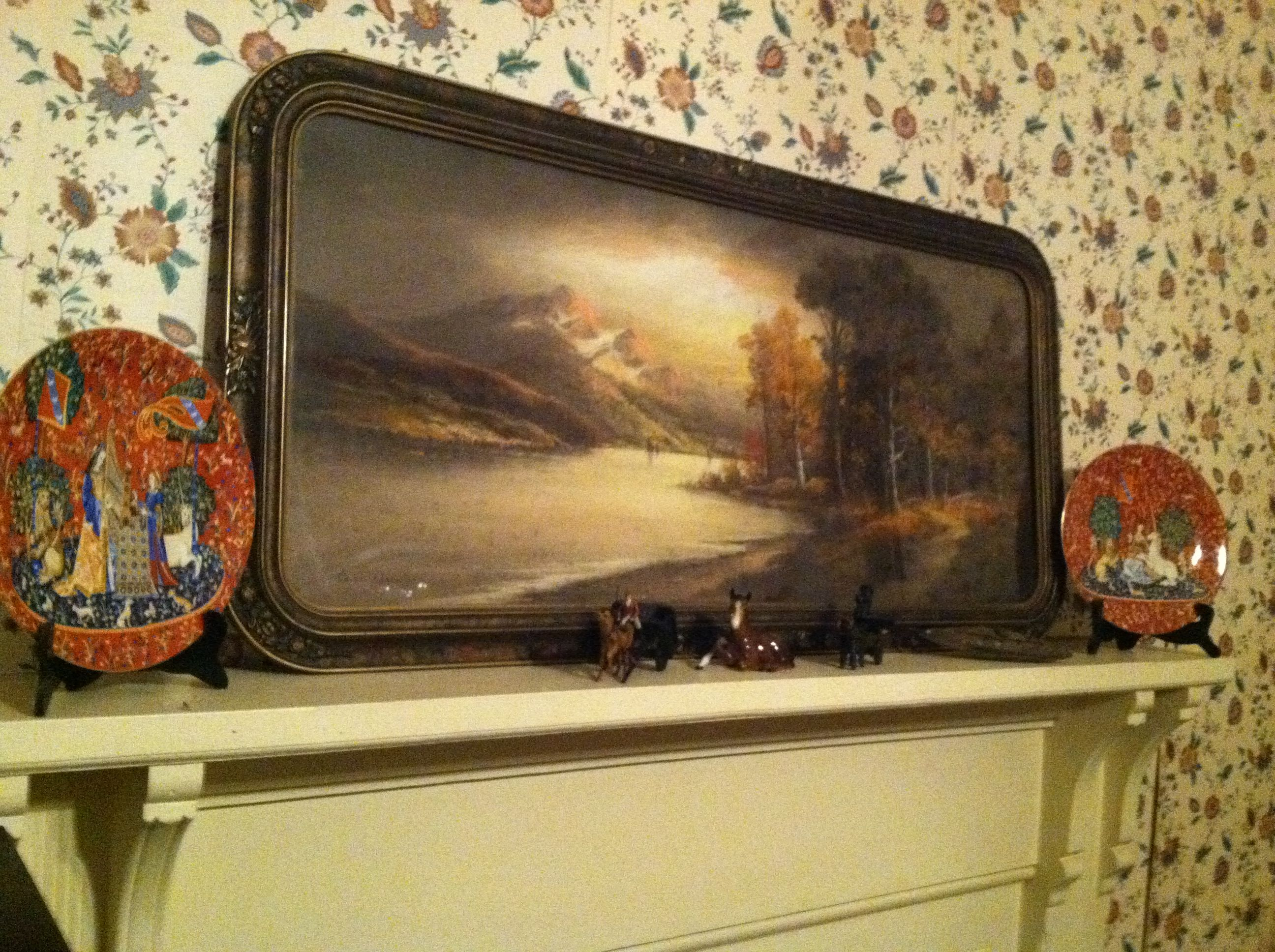 I moved this above the piano. This is a pastel chalk picture, meaning that it is not painted but chalk kind of like chalk on a chalkboard. It is not something you see everyday! My mother had several of these and I have always admired them. There are two in this room. It probably dates back from the mid to late 1800s. The plates on each side are Limoge. I love the little antique toys on the mantel!