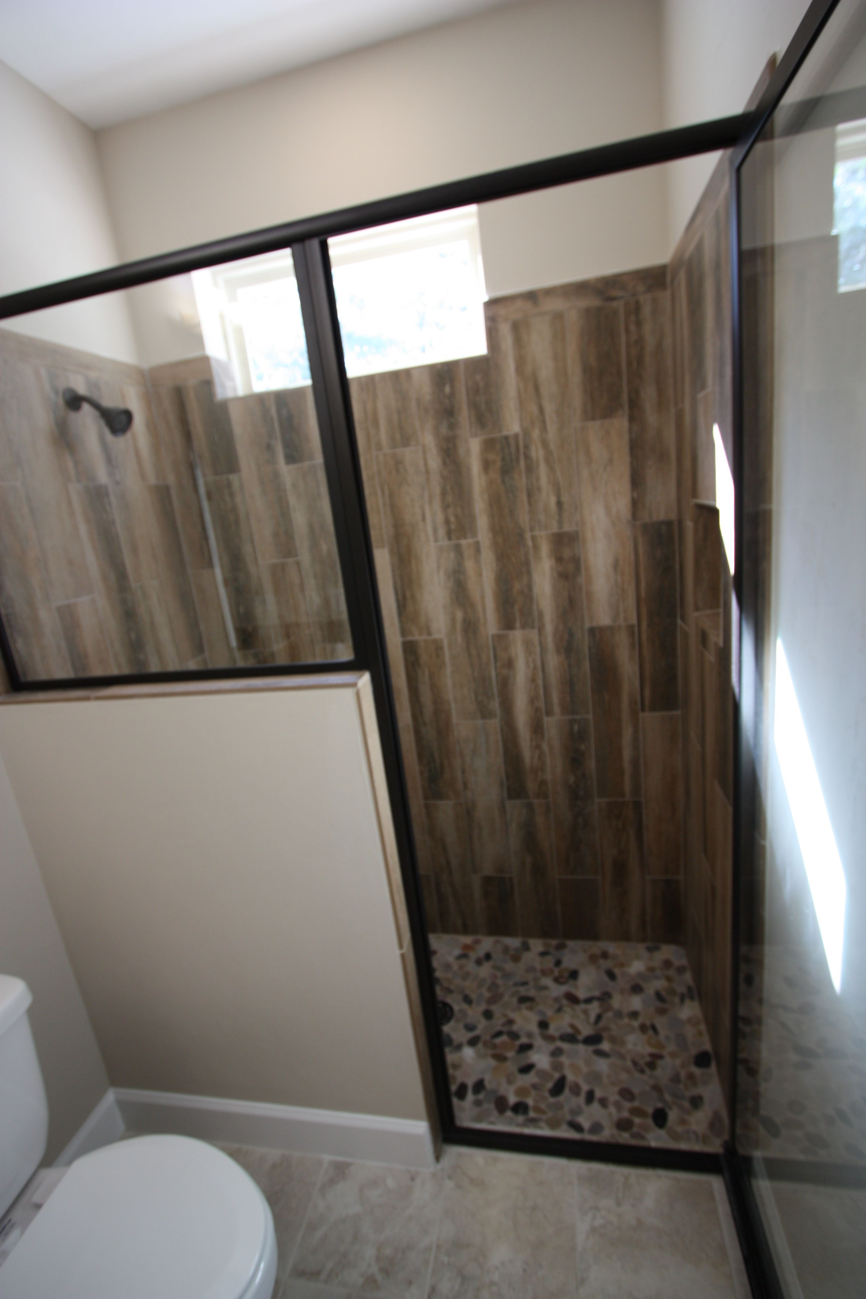 Small Walk In Shower With Pebble Floor And Wood Looking Tile Along