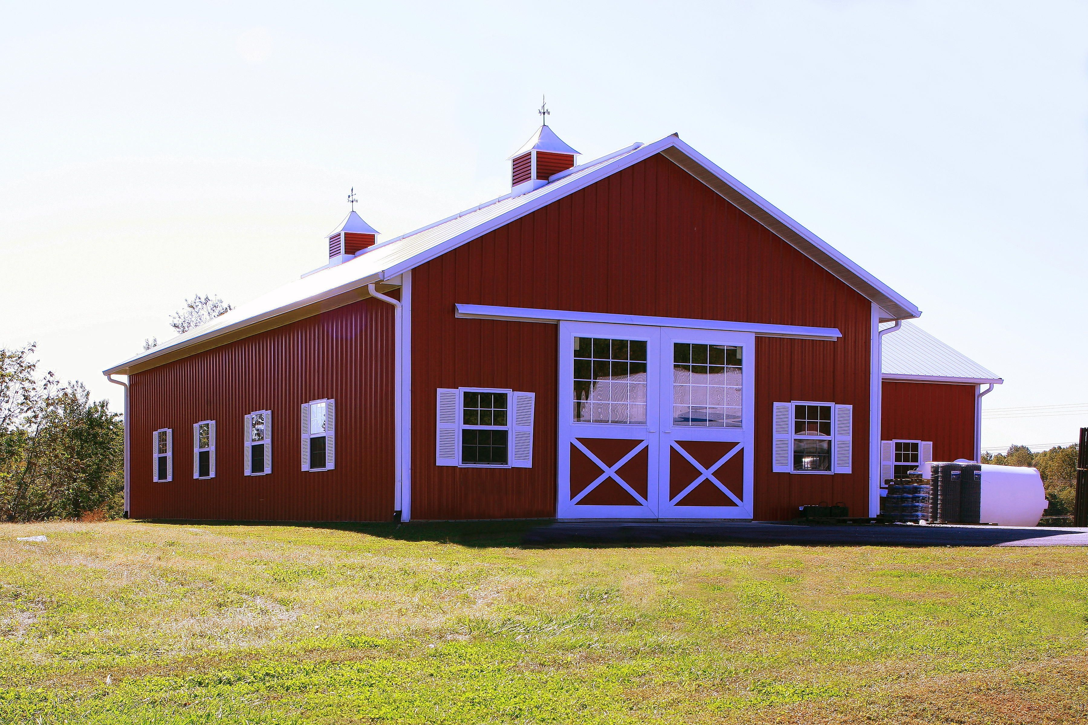 Custom Built Pole Barn Open Space For Storage Brite Red Siding Brite White Roof Trim Copula On Top For Venting Sliding Roof Trim Red Barn Door Building