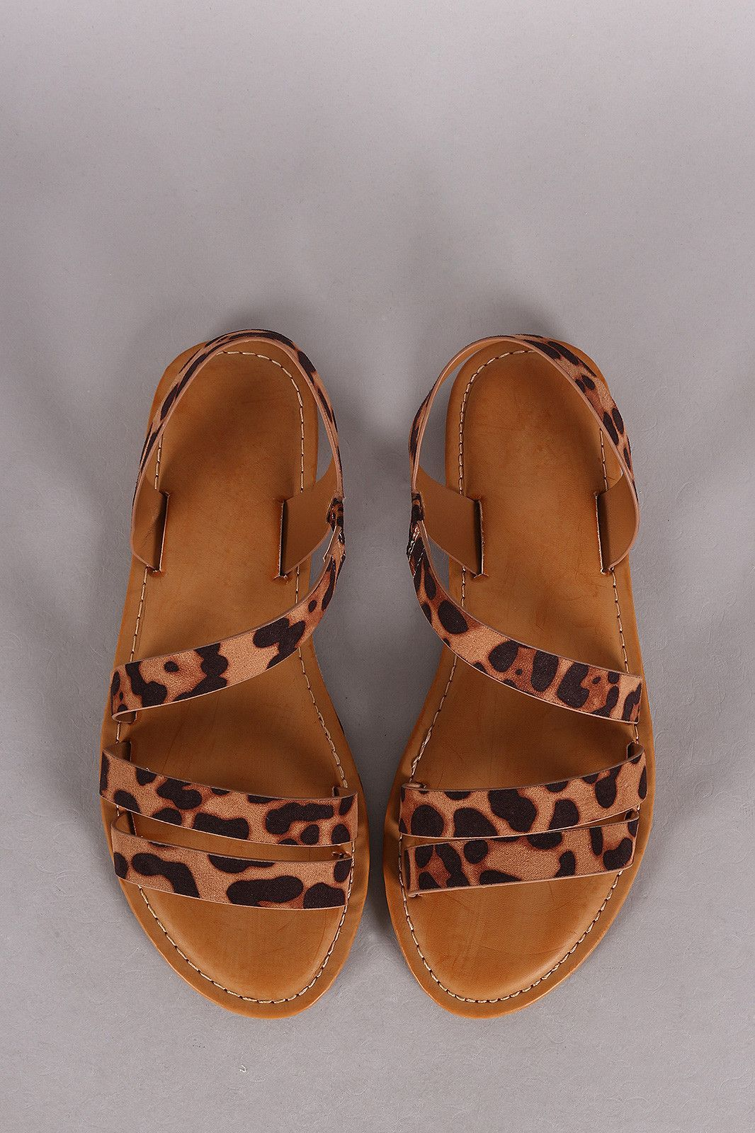 d63abe88bf3e Description This summery leopard print vegan suede upper, open toe  silhouette with asymmetrical strappy construction