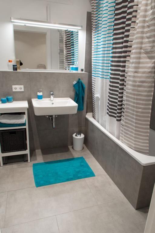 Graue Fliesen, graue Badewanne, blaue Akzente durch Teppich ...