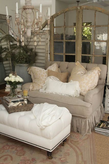 A shabby chic seating area with tufted beige sofa and a white tufted