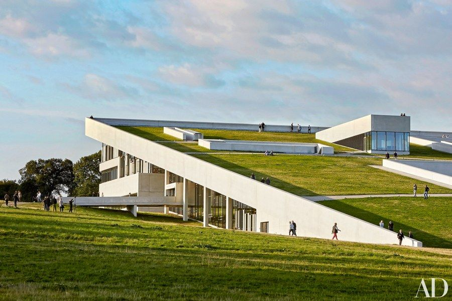 with a sloping green roof that merges with the surrounding terrain this wedge shaped museum of. Black Bedroom Furniture Sets. Home Design Ideas