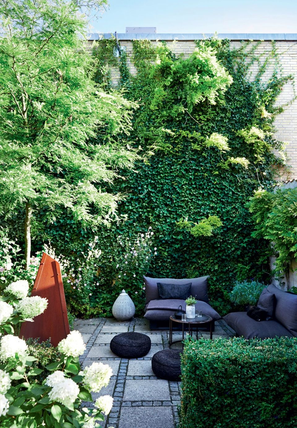 We love the relaxed atmosphere in this green backyard with comfy garden furniture.