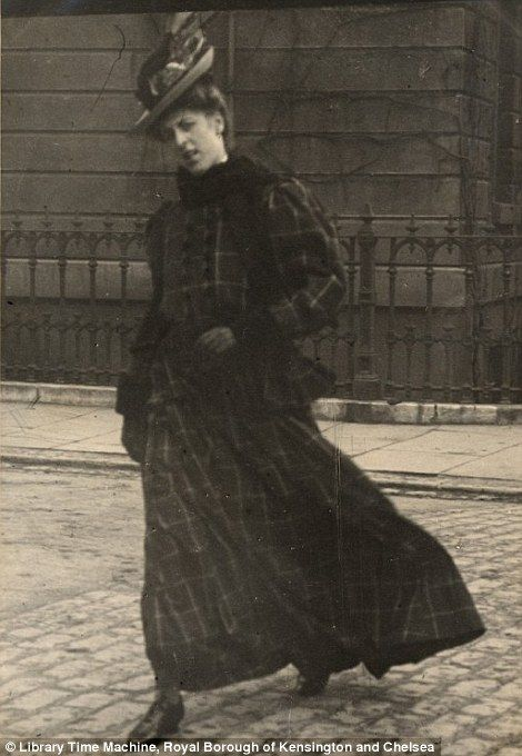 A woman looks in the direction of the camera as she strolls along the street, dressed in an ankle length plaid skirt, matching jacket and a sophisticated hat in Cornwall Gardens on February 20th 1906.