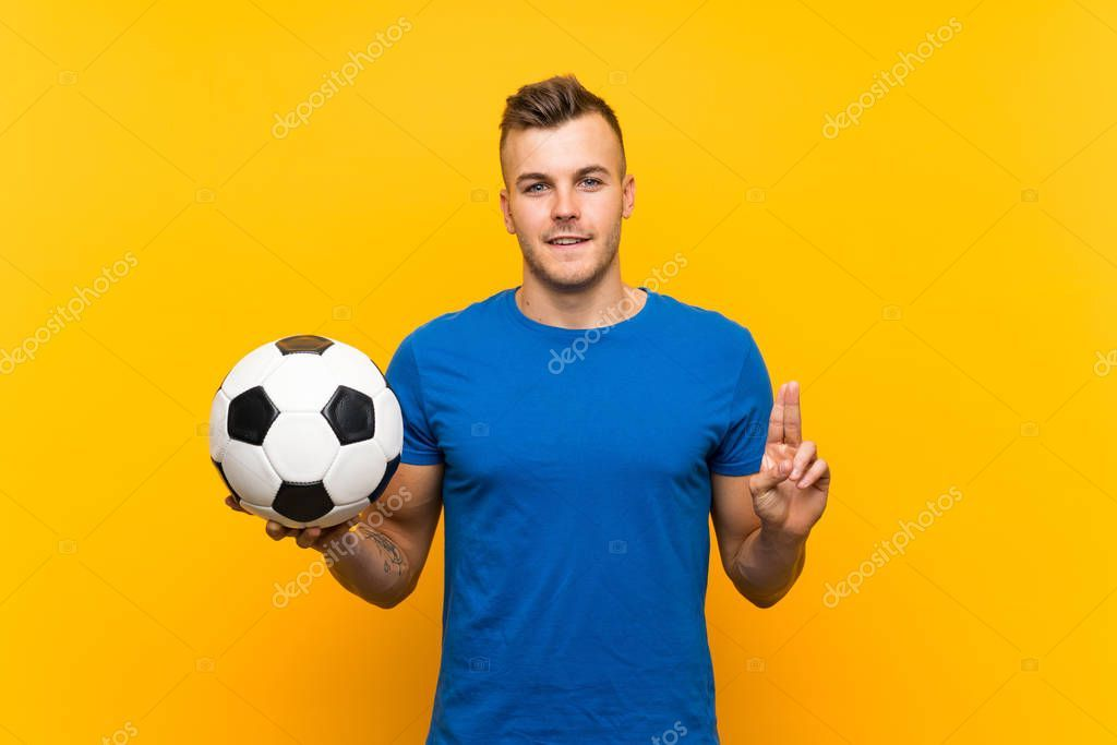 Young Handsome Blonde Man Holding Soccer Ball Isolated Yellow Background In 2020 Blonde Guys Soccer Ball Soccer