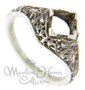 Filigree designs decorate this 14K white gold antique style engagement ring mounting. The ring measures 10.1mm in width and can hold a 5.5mm by 5.5mm emerald cut stone. Made from the original master mold, the mounting can be ordered in 14K or 18K white and yellow gold as well as platinum. Actual prices depend on the current market value of the precious metal used.