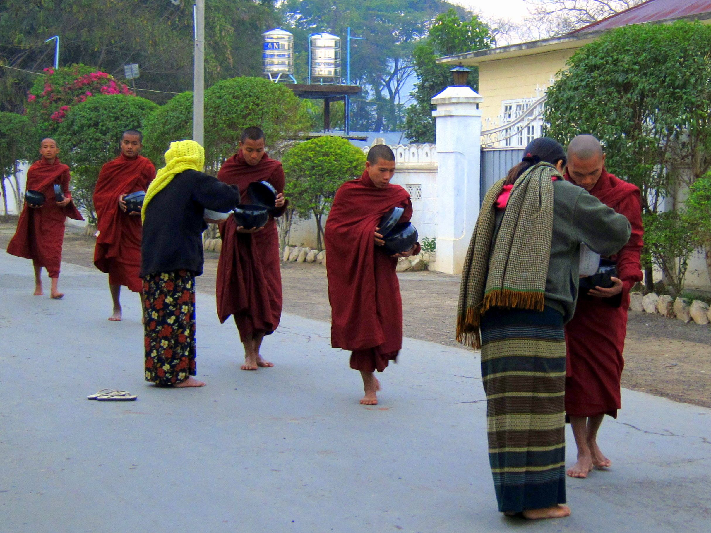 "Offering alms to the monks at dawn on Inle Lake. ""Why I love my Burmese LOngyi"""