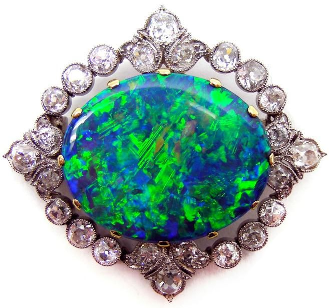 Early 20th century opal and diamond brooch, c 1905, the central blue green opal in gold claw mount, to an old brilliant-cut diamond border, set in platinum, with trefoil detail at the cardinal points, gold pin fitting to the reverse
