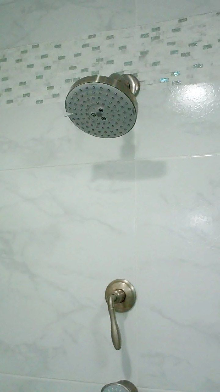 close up of overhead shower head with volume control, inlaid glass bead and marble tile accent strip.