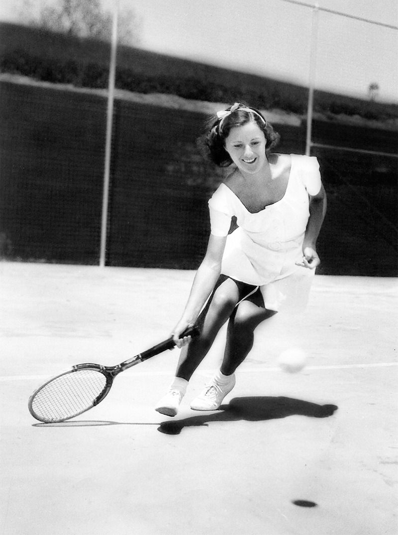 Barbara Stanwyck photographed playing tennis, 1938