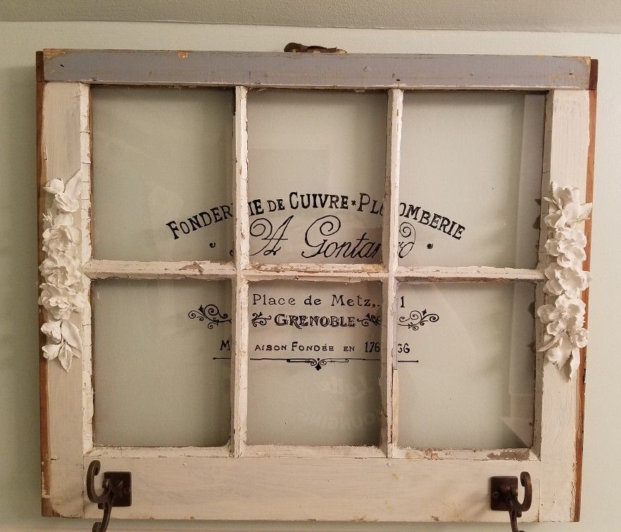Old window with graphic, plaster flowers, and towel hooks added