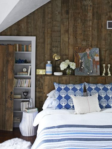 Accents in blue—the painted vase, the printed pillows, and striped quilt—continue the color thread that weaves throughout the house for a cohesive, soothing look.