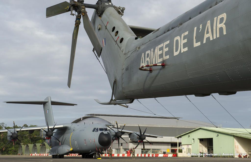 "French Armée de l'Air Airbus Military A400M Atlas aka ""Grizzly"" unsuccessfully trying to hide under the tail of a helicopter. On 10 March 2014 an Atlas of the MEST (Multinational Entry into Service Team) took off from base aérienne 123 Orléans,for the strategic airlifter's first trans Atlantic flight, to America & Caribbean.After 6 hours it touched down at Sal,Cap Verde,& continued to Cayenne,French Guiana & Fort-de-France,Martinique.It carried a load of 2tonnes & a Fennec helicopter to…"