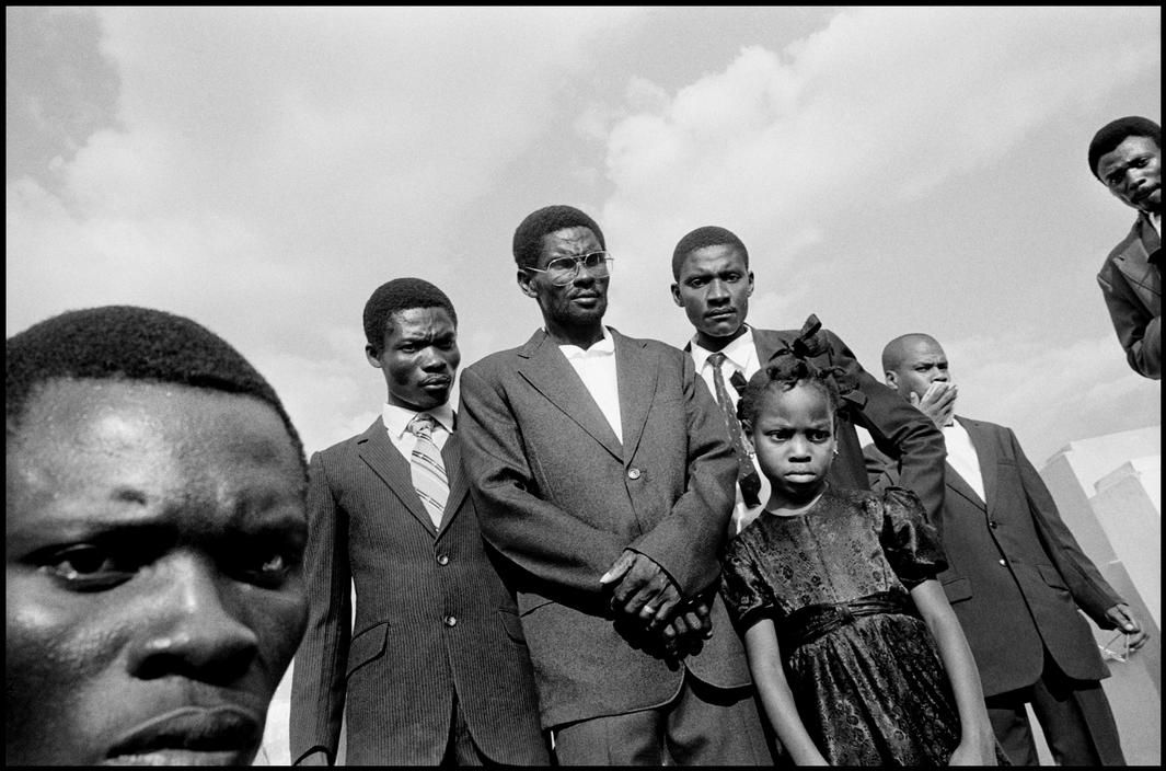 Bruce Gilden Port-au-Prince. 1990. Mourners at a cememtery.