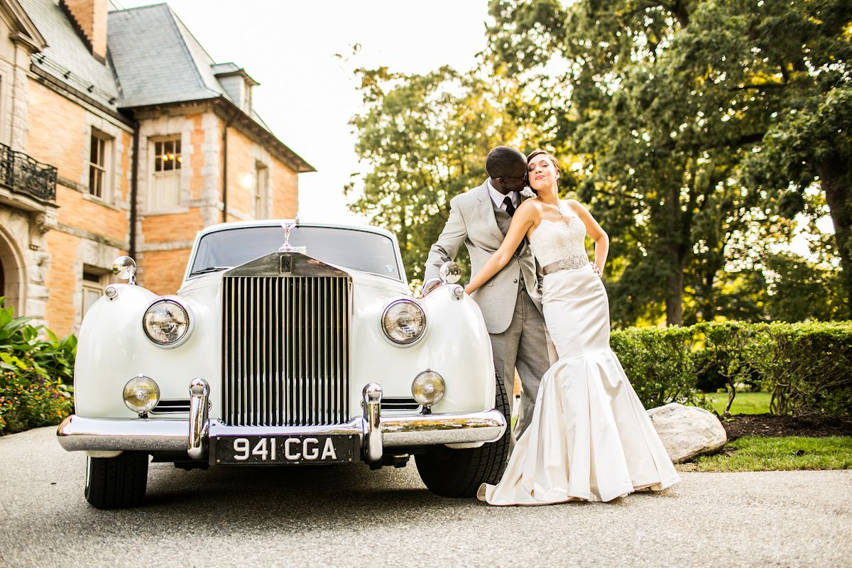 bride and groom standing with Rolls Royce outside
