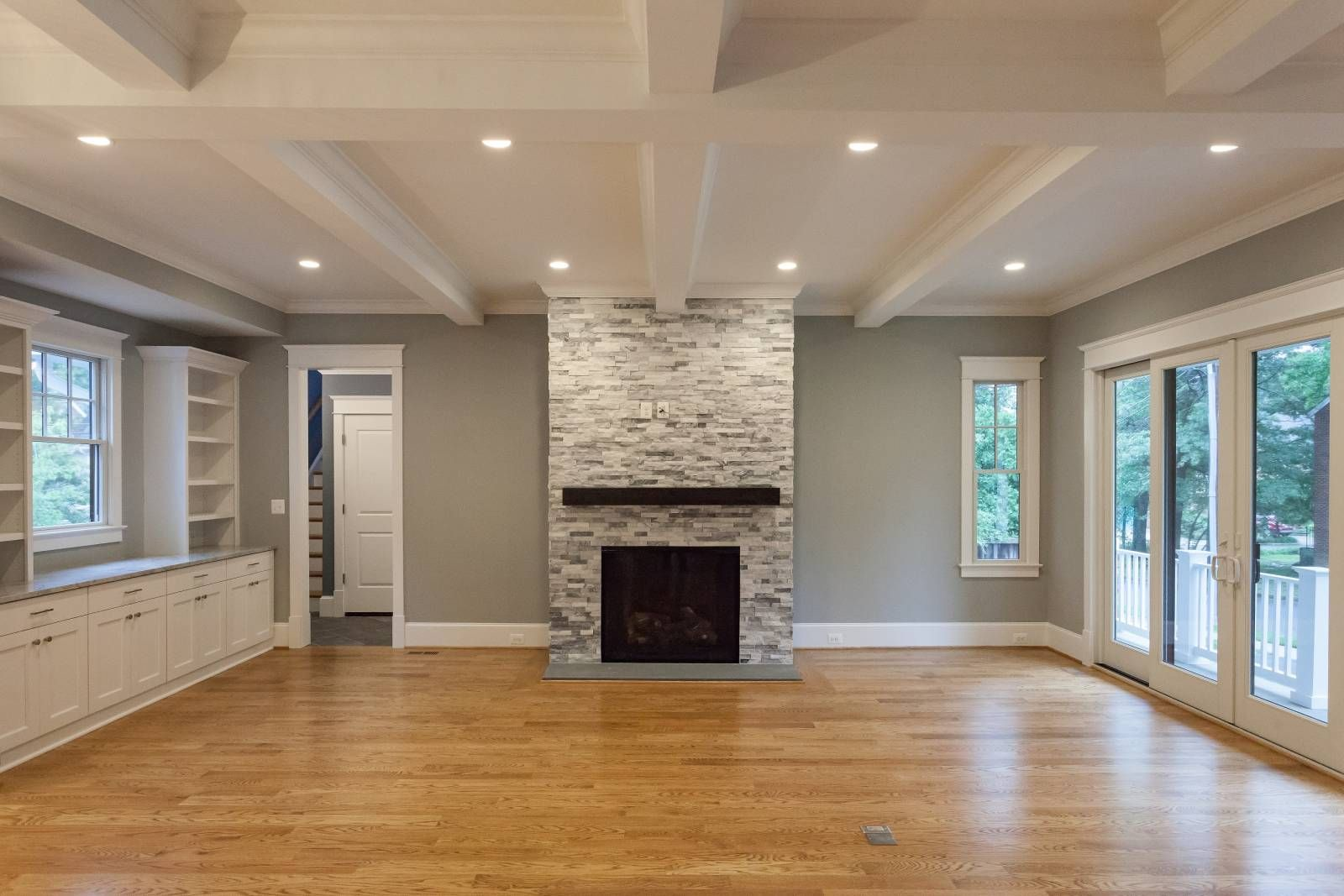 Open concept great room with coffered ceiling, built in ...