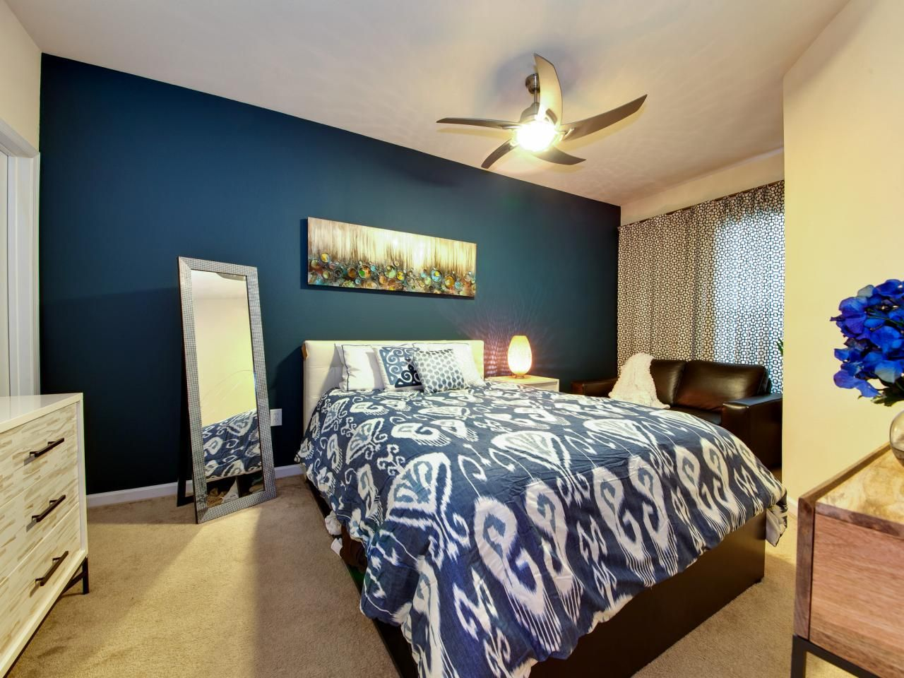 a striking peacock blue accent wall and bold ikat bedding form a