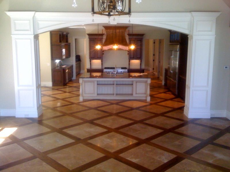 Walnut wide planks mix well with tile floor in this Hardwood and tile floor designs