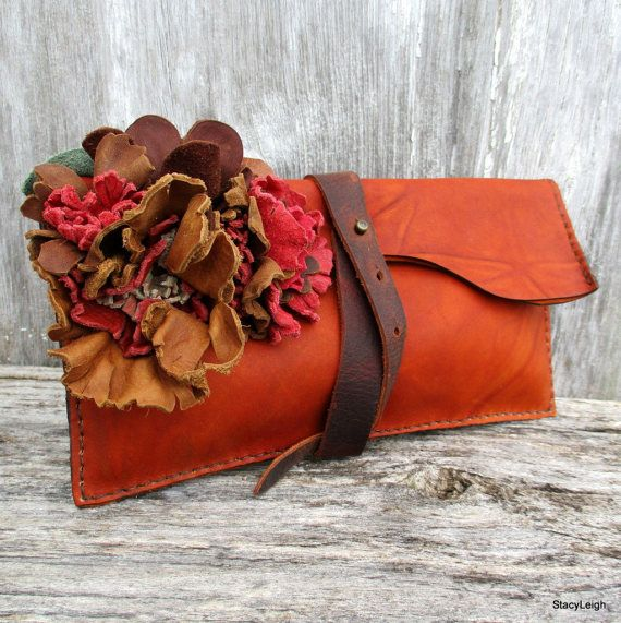 One of a kind leather clutch bag made in a marbled leather in a terracotta brown color. The bag is embellished with a cluster of leather flowers in brown, red, and orange. The bag is 9.5 by 5 and is hand stitched. The bag opens at the top and folds over to close. A leather strap wraps around the bag and fastens over a stud to keep closed. The bag is unlined with no pockets inside.