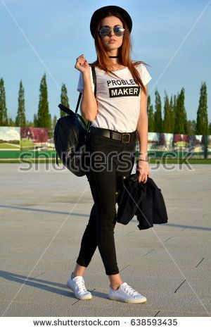 Stylish young woman wearing black hat and backpack modeling on the street