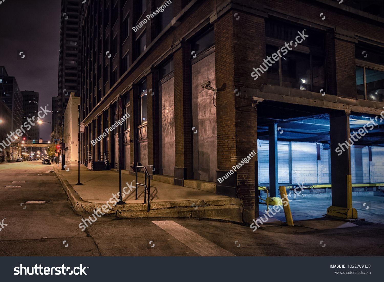 Dark city downtown street corner with an industrial warehouse loading dock at night. #Sponsored , #AD, #street#corner#downtown#Dark