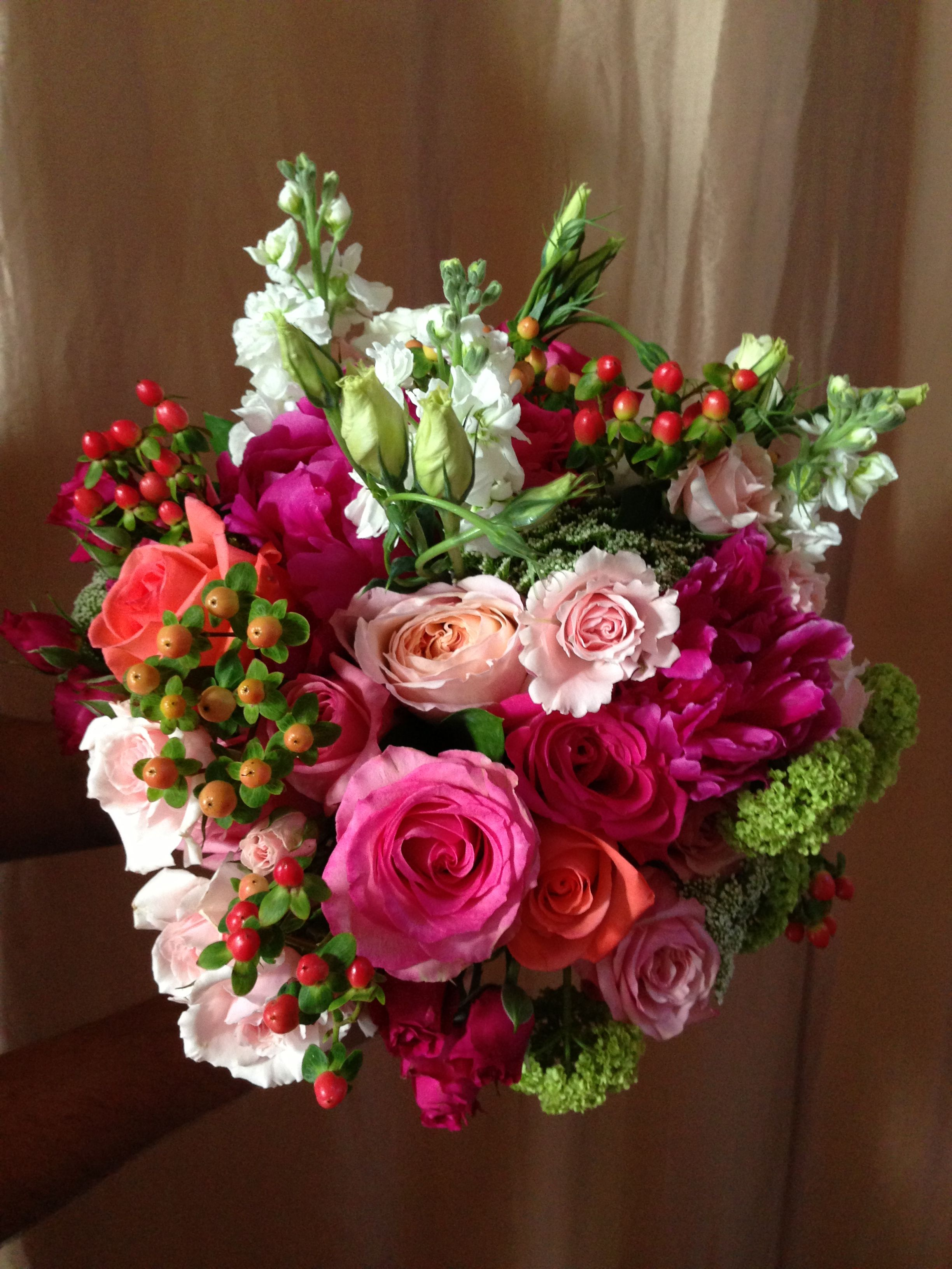 white stock, lisianthus, green viburnum, peach hypericum, light pink roses and spray roses, hot pink roses and peonies