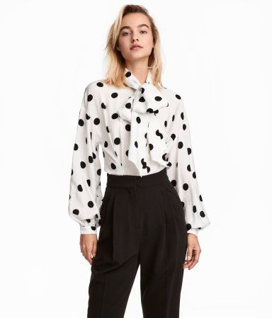 05f83ab42ca3 Weiß Schwarz gepunktet. Bluse aus Viskosestoff mit Punktedruck. Modell mit  Kragen, langen breiten Bindebändern und einer verdeckten Knopfleiste.