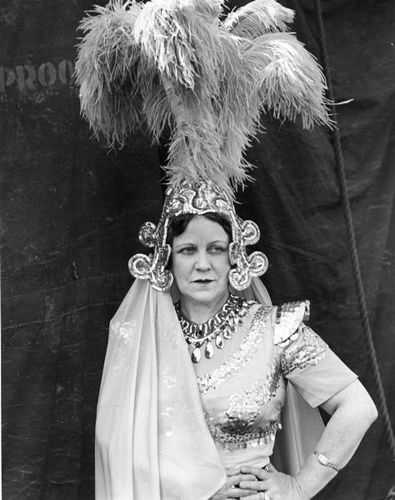 A female Cole Brothers Circus performer is shown in costume, wearing a tall plumed hat, with a tent as a backdrop.